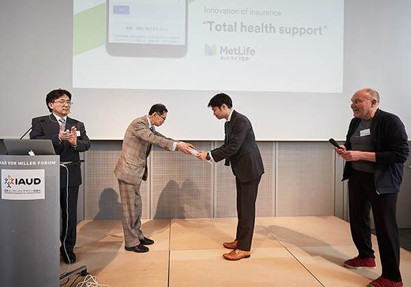 Satoshi Kose übereicht einem Preisträger die Urkunde. Beide verbeugen sich. Roger Coleman und Keiji Kawahara sehen zu.
