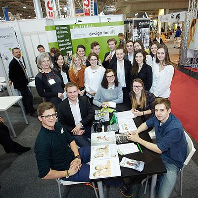 Alle Schüler_innen und design for all-Vorsitzende Veronika Egger am Messestand