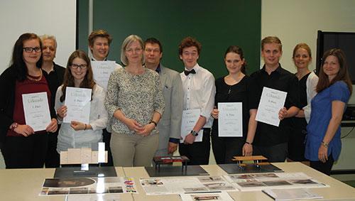 Gewinner_innen, Lehrer und Jury stehen hinter den Modellen der Siegerprojekte und lächeln in die Kamera.