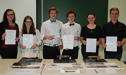 Die Gewinner_innen des Schulwettbewerbs stehen freudestrahlend hinter ihren Modellen und präsentieren stolz die Urkunden.