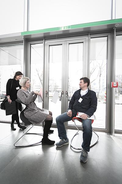 Veronika Egger und Fritz Frenkler testen einen Sessel und diskutieren über die Sitzqualitäten. In Hintergrund Verena Voppivhler.