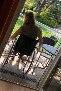 Eine Teilnehmerin sitzt im Rollstuhl mit dem Rücken zum Betrachter, sie steht am Balkon eingerahmt von der Balkontüre.