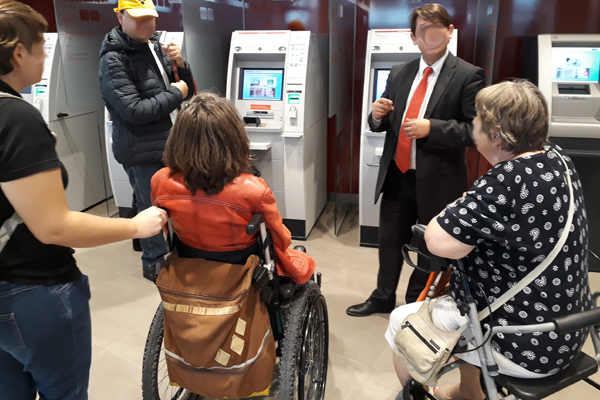 Personen im Rollstuhl und mit Rollator beim Test von Ticketautomaten